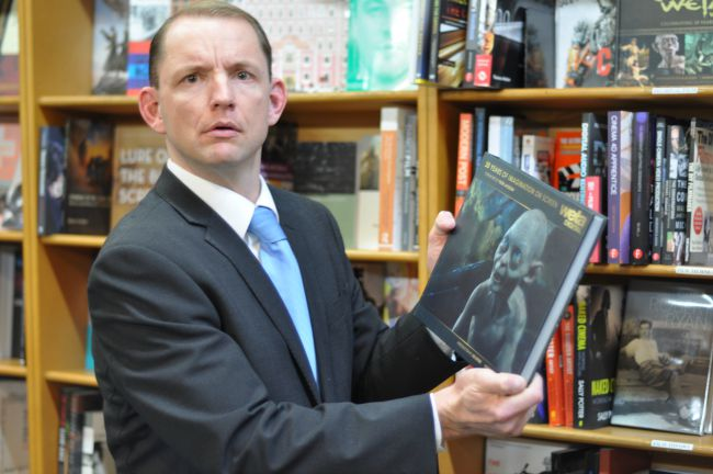 Jonas Holt as Tony Abbott browses the eclectic selection of books at Sydney's book haven, Gleebooks.
