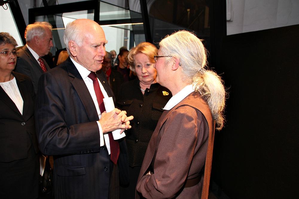 Former Prime Minister John Howard greets Sister Jocelyn Kramer with his wife Janette Howard in the background.